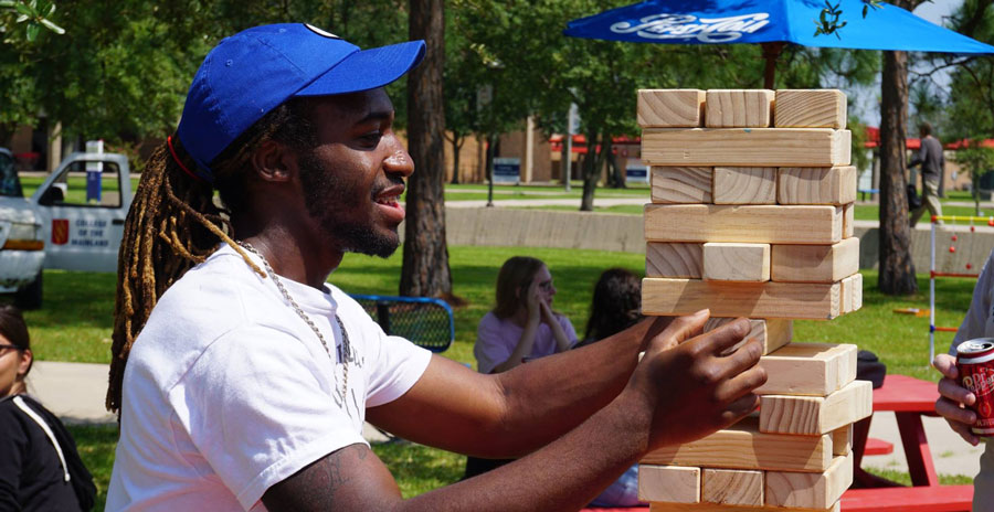 Student playing a giant sized jenga game outside at an event.