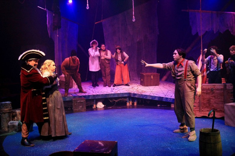 Scene in a play of a pirate holding a young lady hostage while a young man reaches out to her.