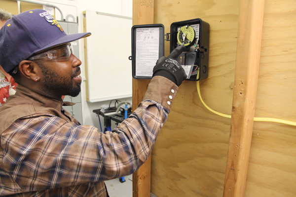 College of the Mainland electrical student Billy Matthews sets a time clock he wired to go on and off at certain times.