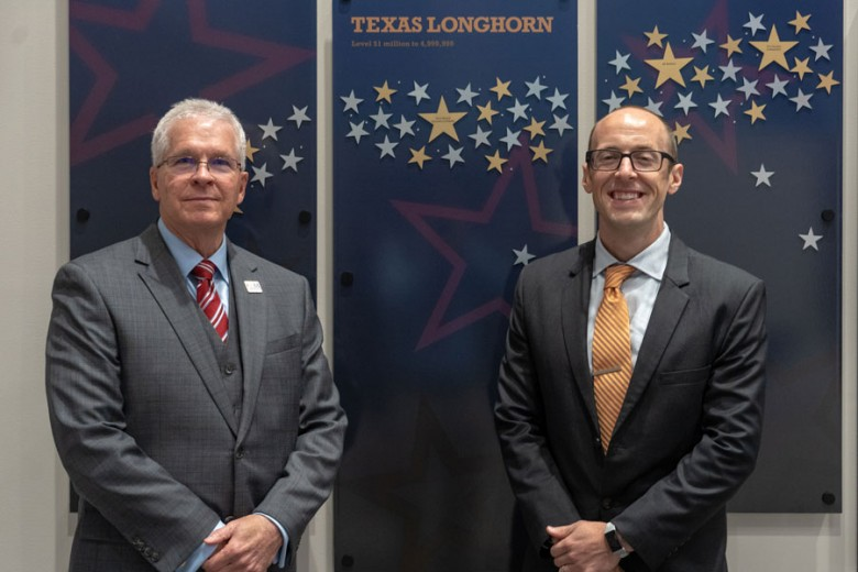 College of the Mainland President Dr. Warren Nichols and Craig Witherspoon, regional safety services manager at Texas Mutual Insurance Company, stand in front of the Donor Recognition Wall.