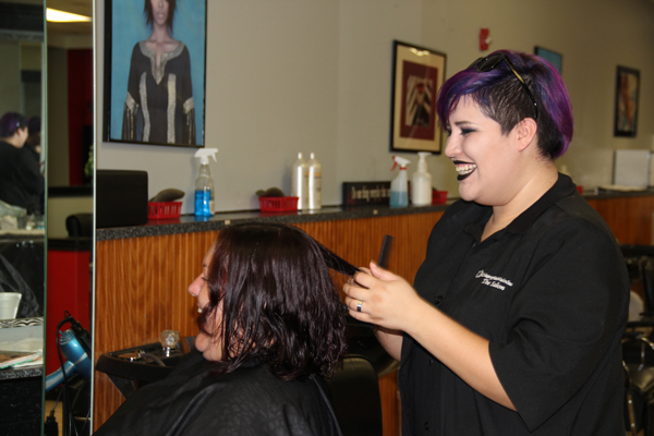College of the Mainland cosmetology student Renee Montemayor styles Stacy Wilson's hair at a day of pampering for women from a Galveston women's shelter.