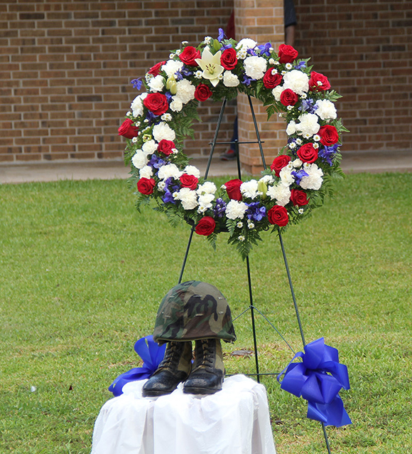A red, white and blue wreath was on display as were a pair of combat boots and helmet and a flag representing each branch of the military.