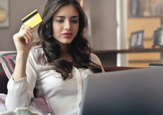 Lady at a laptop computer holding a credit card.