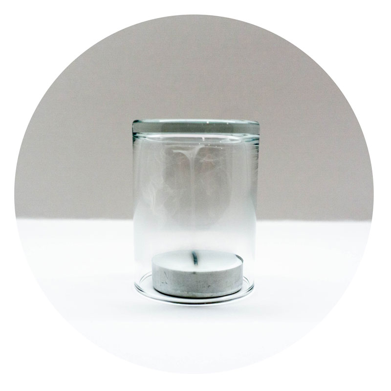 Photo of a tea light covered by a clear glass with smoke inside.