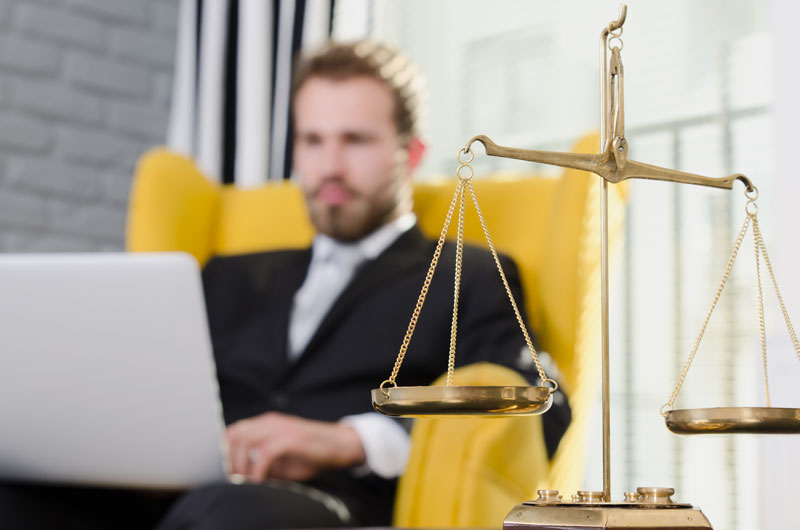 Man sitting in a yellow chair working on his computer with a set of justice scales in front of him.