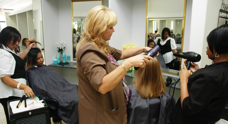 Students in cosmetology class styling hair