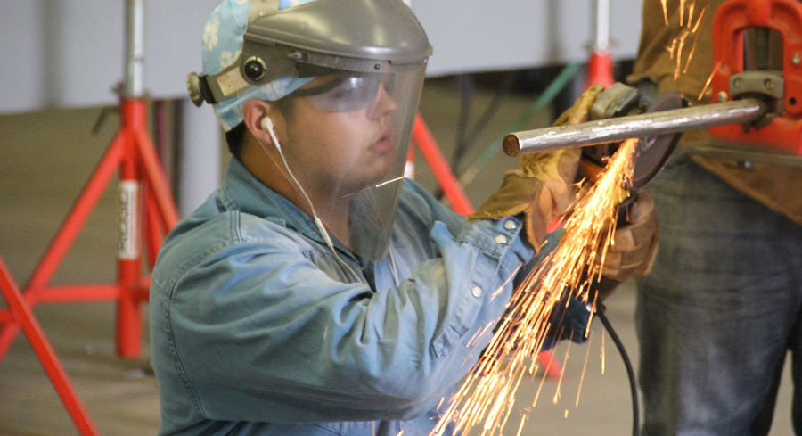Welding student cutting a pipe with a saw