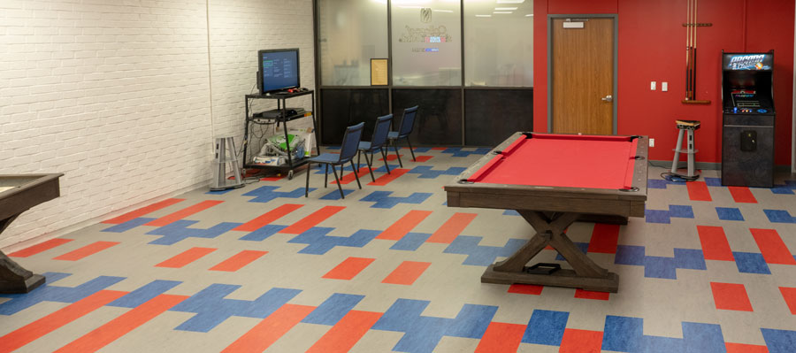 Student recreation room showing a pool table, arcade game, and video game station.
