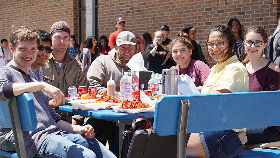 Large group of students eating outside at an event