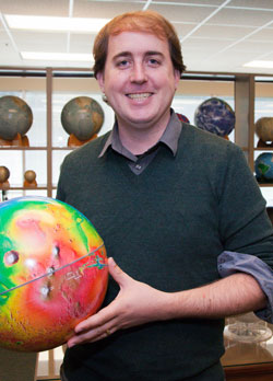 Nicholas Castle holding a colorful globe of the earth