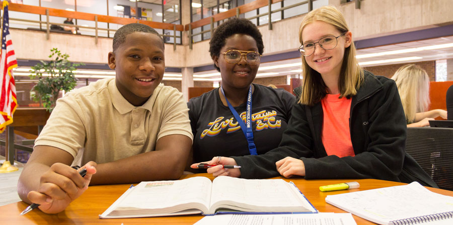 Three TRIO students studying together in the library.